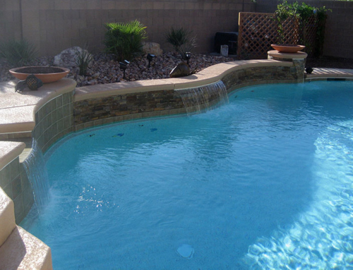 Custom pool with natural rock waterfall with stamped for Custom pool and spa