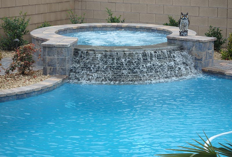 Custom pool and raised spa with stacked stone spillway for Custom pool and spa